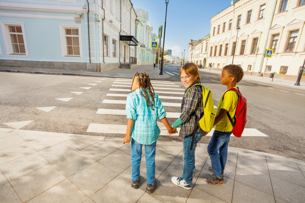 Three kids holding hands stand on street ready to cross the road in the city during summer